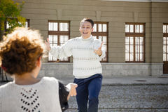 Девушка распологая на стенд пока человек в предпосылке развевая для того чтобы повернуть towa стоковое фото rf