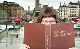 Девушка рассматривает английские словарь и квадрат Стоковые Фото