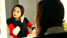 Девушка расчесывает ее волосы и подготавливает на дата на зеркале видеоматериал