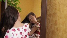 Девушка расчесывает ее волосы зеркалом Маленькая девочка расчесывает ее волосы Ребенок сидит зеркалом сток-видео