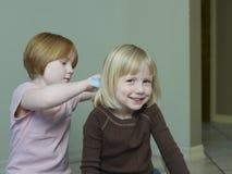 Девушка расчесывая светлые волосы сестры Стоковая Фотография