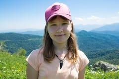 Девушка ребенка в горах на зеленой траве стоковое изображение
