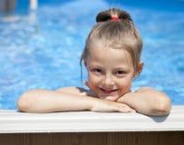 Девушка ребенка в голубом бикини около бассейна горячее лето Стоковые Изображения