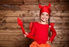 Девушка ребенка в костюме дьявола к хеллоуину на деревянном Стоковые Фото