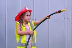 Девушка ребенка в костюме пожарного Стоковые Фотографии RF