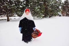 Девушка ребенка в меховой шыбе и головной платок в русском стиле держа плетеную корзину в руках стоковые фотографии rf
