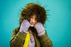 Девушка ребенка в теплой куртке осени с клобуком меха в зеленом цвете и mittens, съемкой на сини изолировала предпосылку стоковые фото