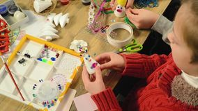 Девушка ребенка делает украшение на праздники Ремесла и игрушки, рождественская елка и другое Акварели картины Взгляд сверху asam сток-видео