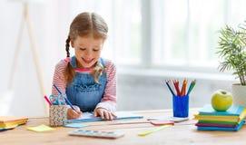 Девушка ребенка делая сочинительство и чтение домашней работы дома стоковая фотография rf