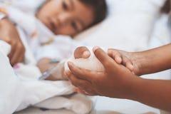 Девушка ребенка держа больную молодую руку сестры которое имеет решение IV перевязанное с любовью и заботой стоковые фотографии rf