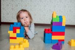 Девушка ребенка лежа около ярких пластичных блоков конструкции Малыш играя на поле Превращаясь игрушки раньше учащ Стоковые Фотографии RF