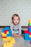 Девушка ребенка лежа около ярких пластичных блоков конструкции Малыш играя на поле Превращаясь игрушки раньше учащ Стоковая Фотография