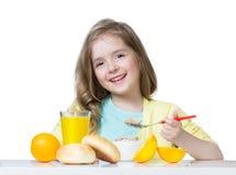 Девушка ребенка есть на таблице изолированной на белизне Стоковые Изображения RF