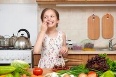 Девушка ребенка ест вишни, фрукты и овощи в домашней кухне i Стоковые Фотографии RF