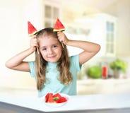 Девушка ребенка ест космос предпосылки арбуза внутри помещения пустой Стоковая Фотография