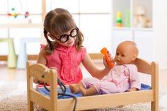 Девушка ребенка играет пациента куколки доктора рассматривая с otoscope игрушки стоковое фото rf