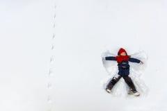 Девушка ребенка играя в снеге Стоковые Фотографии RF