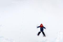 Девушка ребенка играя в снеге Стоковое Изображение RF