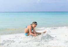 Девушка ребенка играя на пляже белого песка шикарном около океана Стоковая Фотография RF