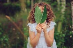 Девушка ребенка играя с листьями в исследовании природы леса лета с детьми Стоковые Фотографии RF