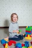 Девушка ребенка имея потеху и строение ярких пластичных блоков конструкции Малыш играя на поле Превращаясь игрушки Предыдущее lea Стоковое Изображение RF