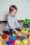 Девушка ребенка имея потеху и строение ярких пластичных блоков конструкции Малыш играя на поле Превращаясь игрушки Предыдущее lea Стоковое Фото