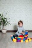 Девушка ребенка имея потеху и строение ярких пластичных блоков конструкции Малыш играя на поле Превращаясь игрушки Предыдущее lea Стоковые Фото