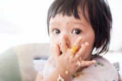 Девушка ребенка милого младенца азиатская есть здоровую еду сама стоковое изображение