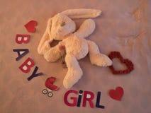 Девушка ребенка надписи выровнянная на кровати Символ капусты беременности Зайцы и сердце лежат на кровати Стоковые Изображения