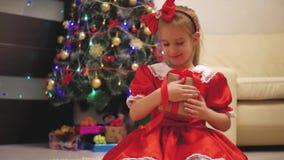 Девушка ребенка нося красное платье раскрывая Xmas представляет Счастливая маленькая усмехаясь девушка с подарочной коробкой рожд акции видеоматериалы