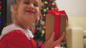 Девушка ребенка нося красное платье раскрывая Xmas представляет Счастливая маленькая усмехаясь девушка с подарочной коробкой рожд сток-видео