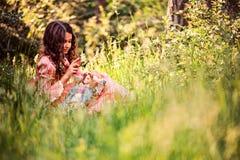 Девушка ребенка одетая как принцесса сказки играя с куклой в лесе лета Стоковые Фото