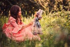 Девушка ребенка одетая как принцесса сказки играя с куклой в лесе лета Стоковое фото RF