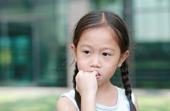 Девушка ребенка планирует сосущ ее пальцы Жесты детей которые нуждаются доверии стоковые изображения rf