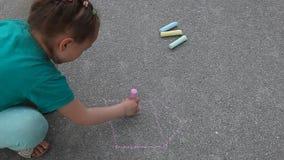 Девушка ребенка рисует с мелом на конце асфальта вверх по внешнему видеоматериал