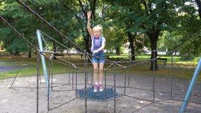 Девушка ребенка скача на спортивную площадку видеоматериал