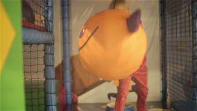 Девушка ребенка тряся смешной шарик с улыбкой Маленькая красивая девушка играя в игровой детей сток-видео