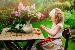 Девушка ребенка украшая торты с цветками на чаепитии сада весной Стоковое Изображение RF