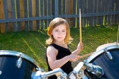 Девушка ребенк барабанщика белокурая играя барабанчики в задворк tha Стоковая Фотография