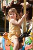 Девушка ребенк в лошади carousel рядом с женщиной Стоковые Изображения RF