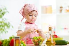 Девушка ребенк кашевара подготавливая овощи Стоковое Изображение RF
