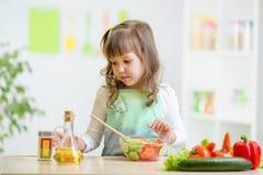 Девушка ребенк подготавливая овощи Стоковая Фотография