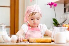 Девушка ребенк подготавливая тесто в кухне Стоковая Фотография RF