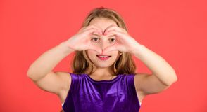 Девушка ребенк прелестная с жестом сердца шоу стороны длинных волос усмехаясь к вам Отпразднуйте день валентинок Любовь и сочувст стоковое изображение