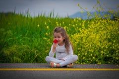 Девушка ребенк сидя на дороге Стоковое Изображение RF