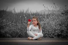 Девушка ребенк сидя на дороге Стоковые Изображения RF