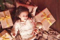 Девушка ребенк с подарками на рождество под деревом chrismas Стоковое Изображение RF