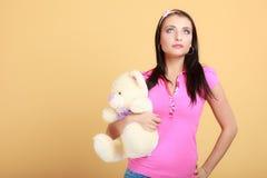 Девушка ребяческой молодой женщины ребячья в розовой обнимая игрушке плюшевого медвежонка Стоковые Фотографии RF