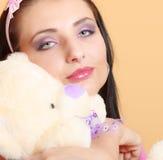 Девушка ребяческой молодой женщины ребячья в розовой обнимая игрушке плюшевого медвежонка Стоковые Фото