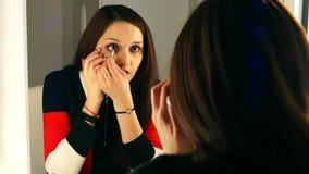 Девушка регулирует ее волосы на зеркале и восхищает ее отражение акции видеоматериалы